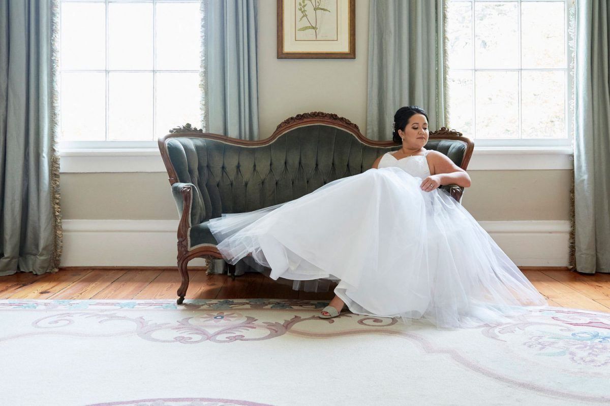 Editorial lifestyle photo of a bride in her wedding dress lying on a leather couch