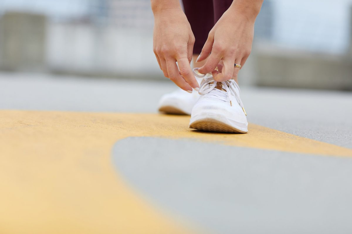 Editorial lifestyle photography of a woman's hands tying the laces on a pair of white sneakers