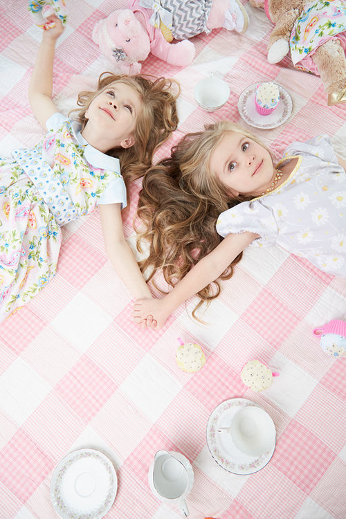 Editorial lifestyle photography of two young girls dressed in pink having a tea party