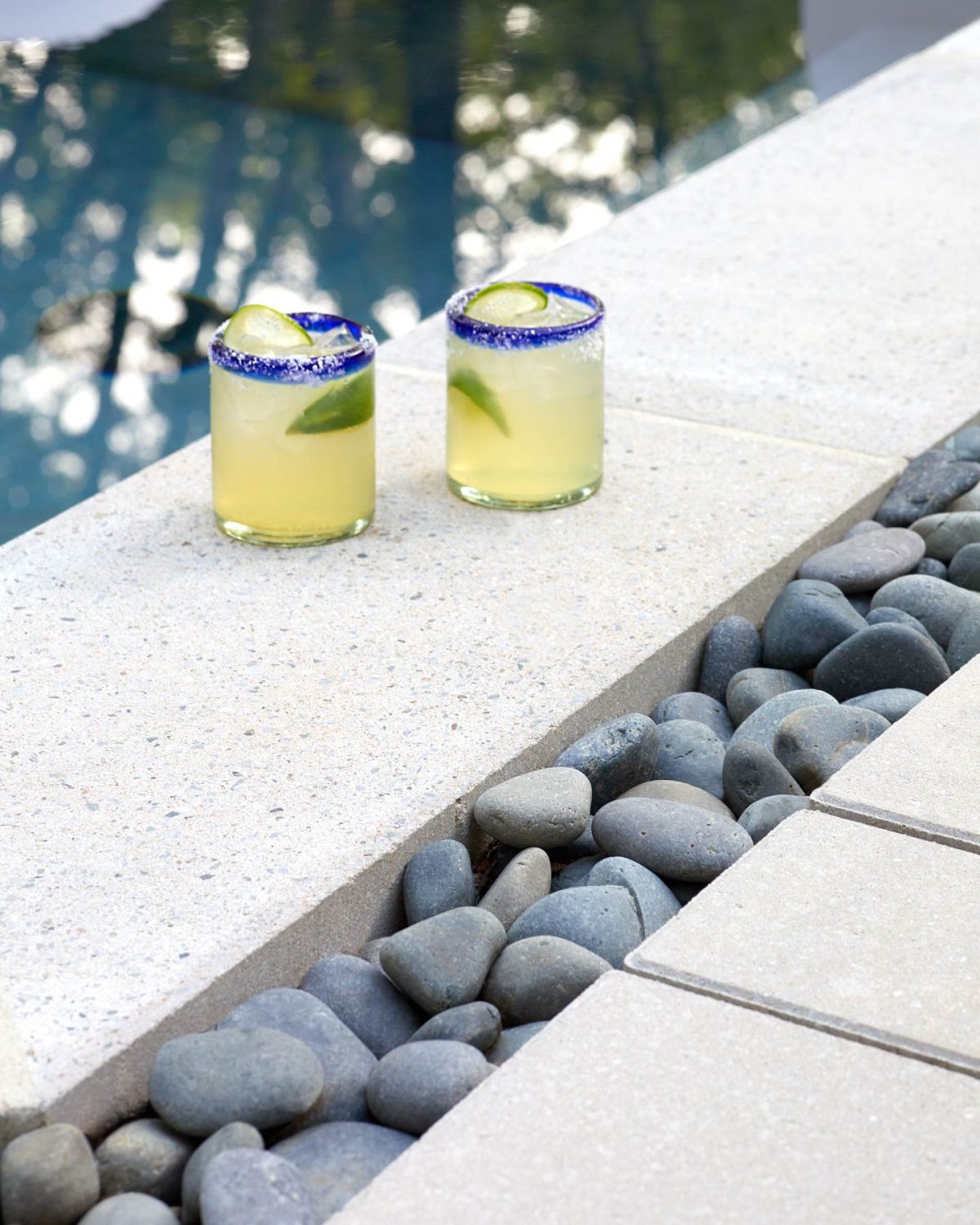 Editorial lifestyle photography of two colorful cocktails on the edge of a modern outdoor pool