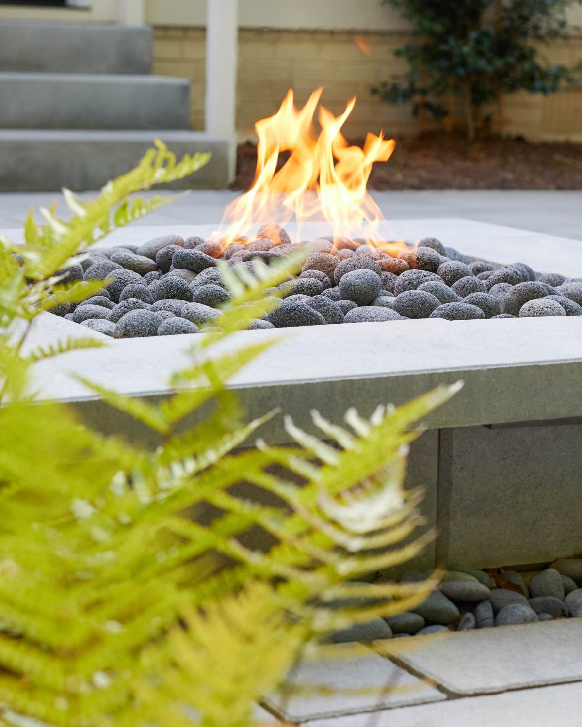 Editorial lifestyle photo of an outdoor stone fireplace