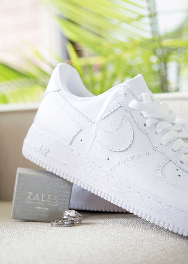 Editorial lifestyle photo of a pair of women's white Nike sneakers and a jewelry box from Zales