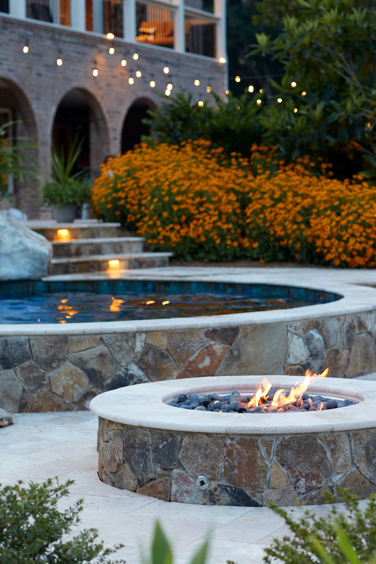 Editorial lifestyle photo of a modern outdoor deck and patio area with a stone fireplace and pool
