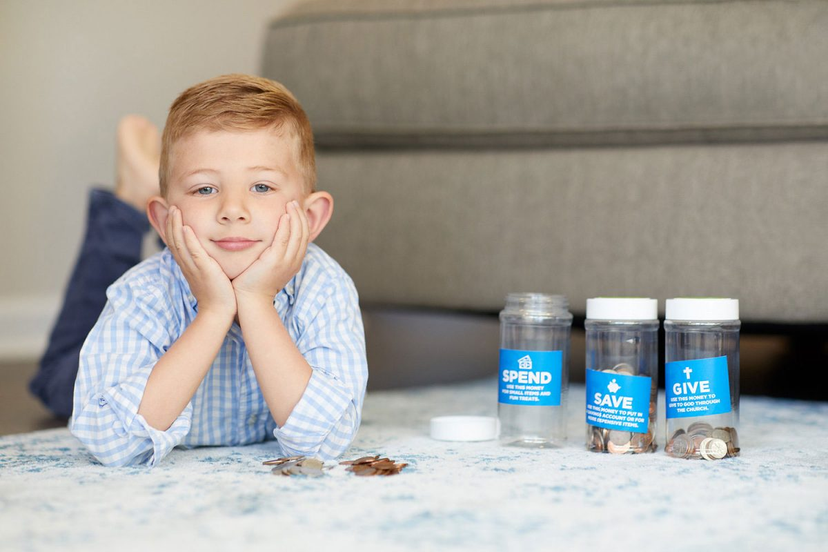 Editorial lifestyle photo of a young boy sitting on a bed with three coin banks