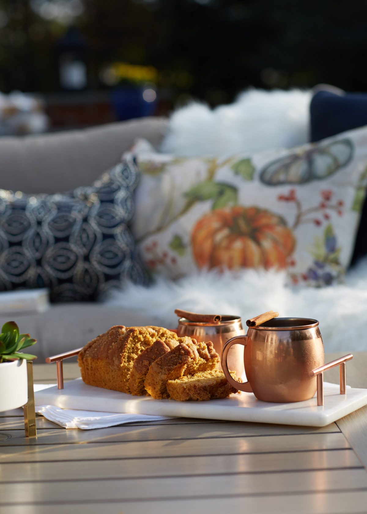 Editorial lifestyle photo with a tray of pumpkin bread and beverages in copper mugs on an outside table