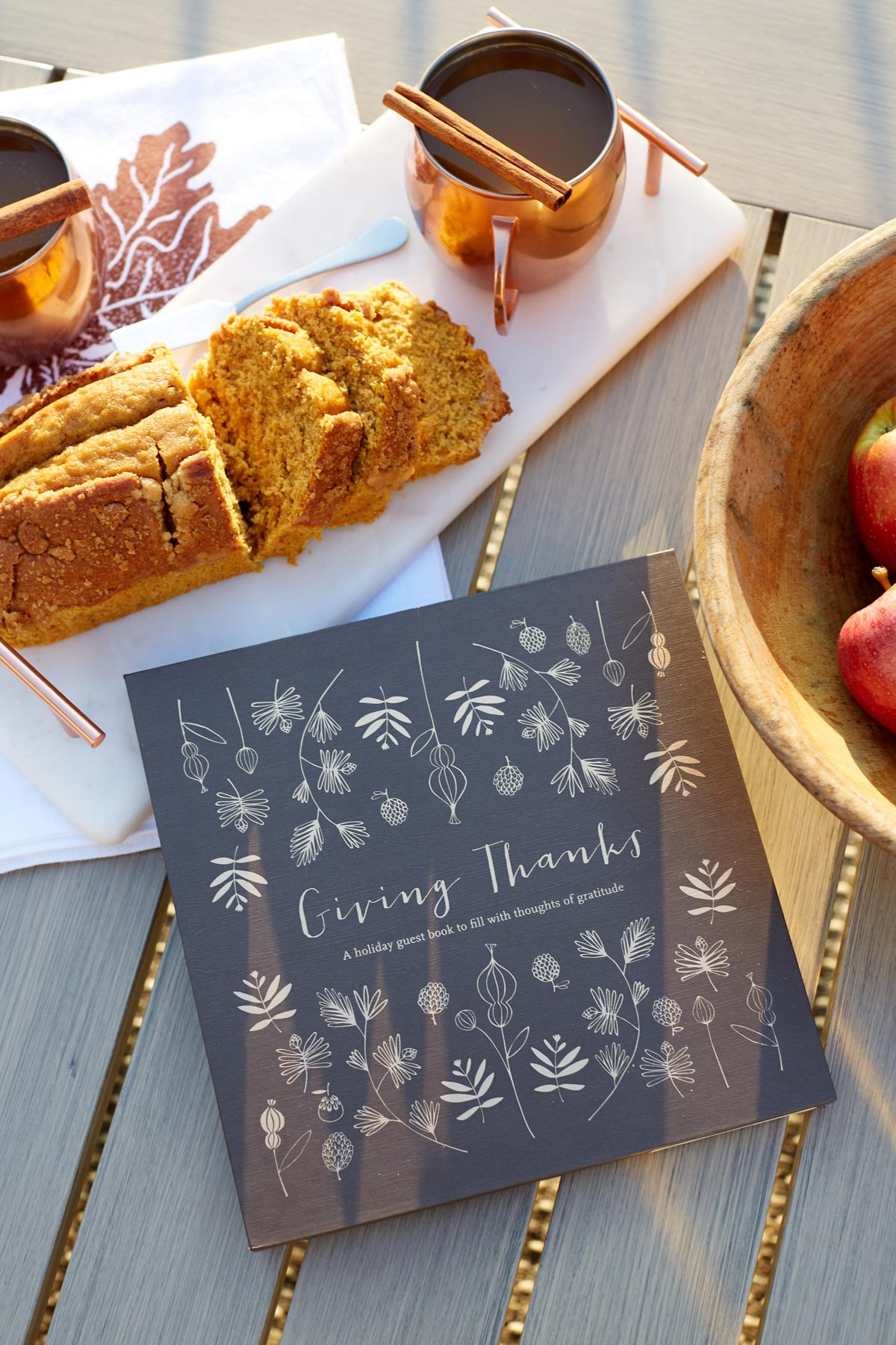 Food lifestyle photo of a loaf of pumpkin bread on a white tray alongside copper mugs filled with spiced cider