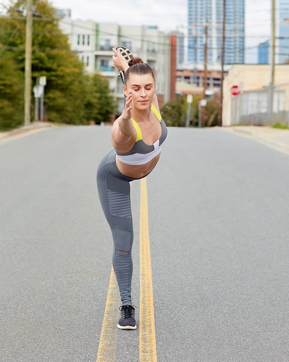 Editorial fitness photography of a female model doing yoga in the road