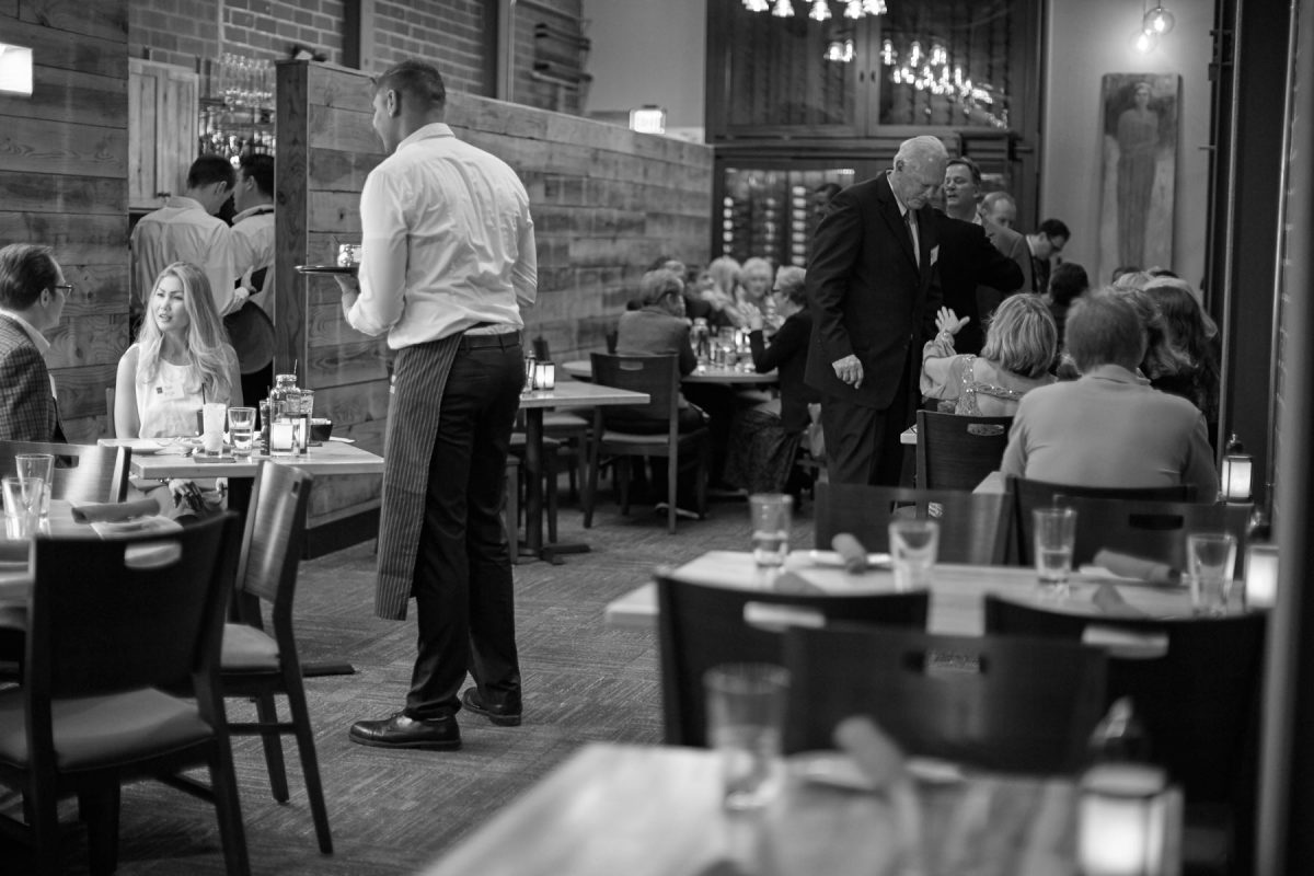 Interior photo of a waiter serving a table at a busy, modern resaturant