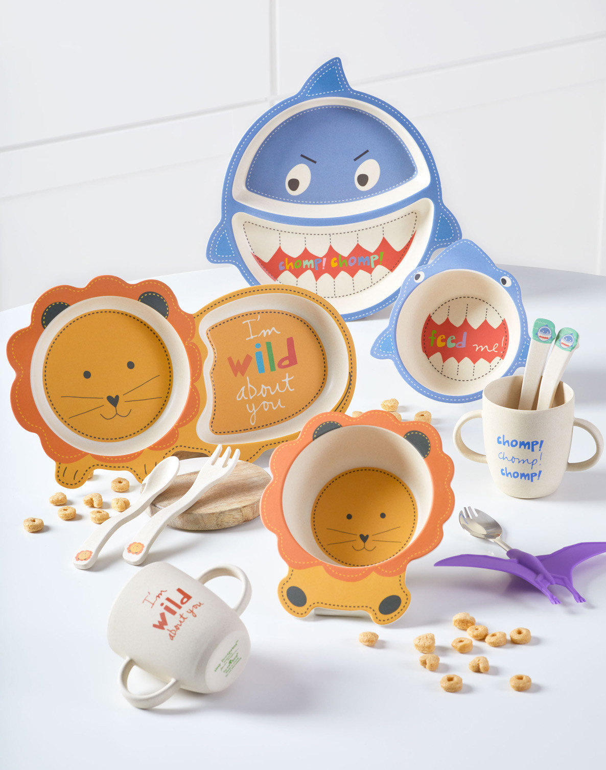 Lifestyle product photography showing a collection of plates, bowls, and eating utensils designed for children