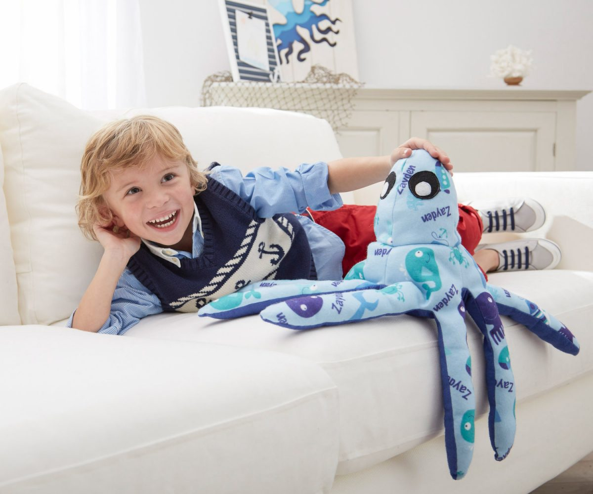 Lifestyle product photography of a happy young boy playing with a plush octopus toy on a couch
