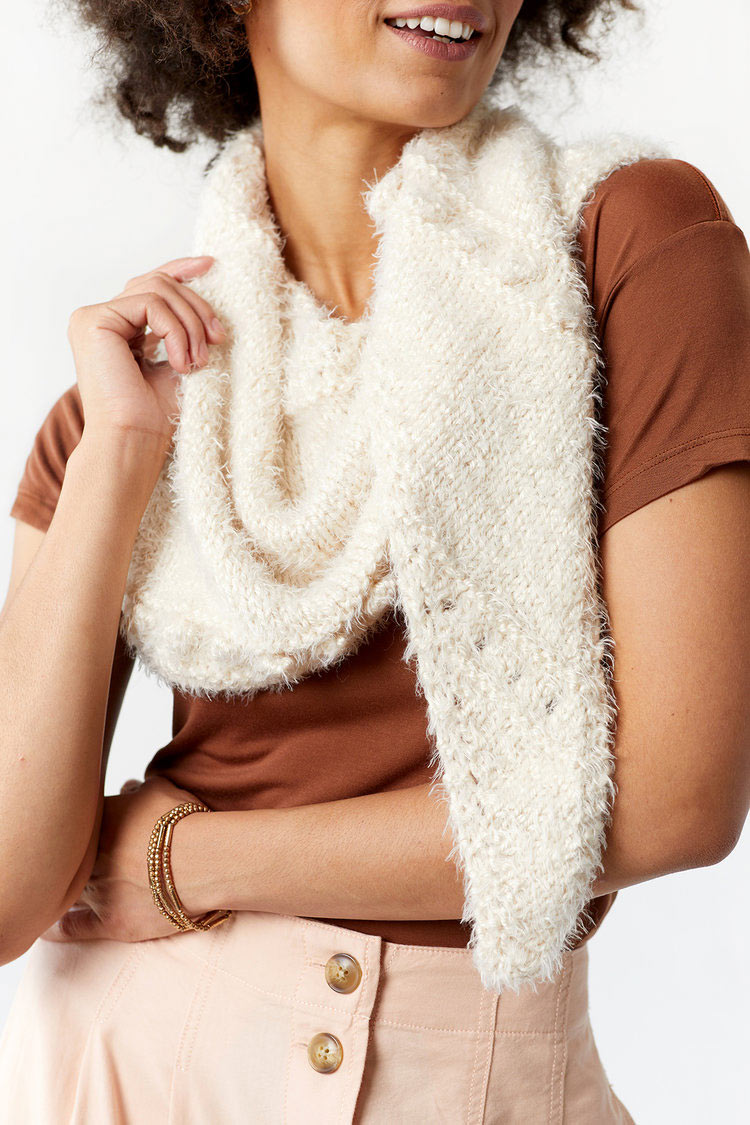 Lifestyle product photography of female model wearing a hand knit ivory colored scarf