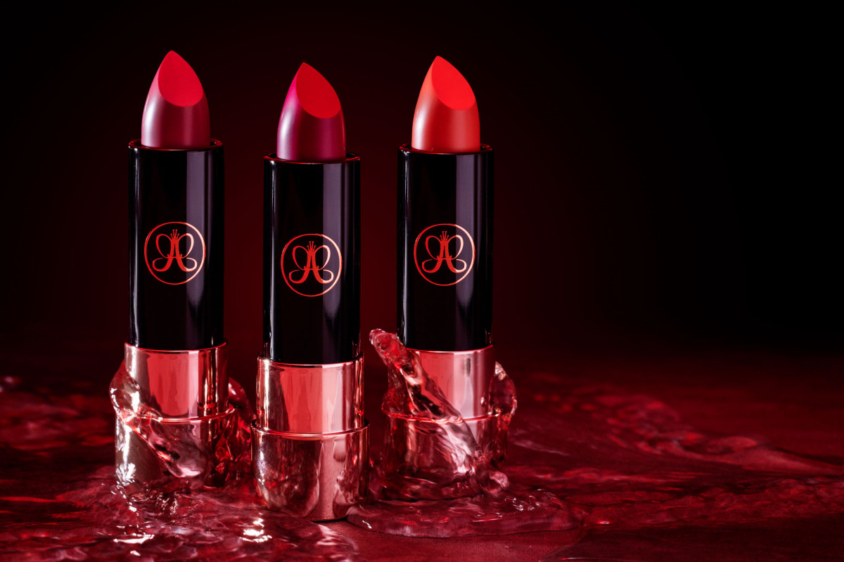 Striking lifestyle product photo of luxury red lipstick tubes against a black backdrop