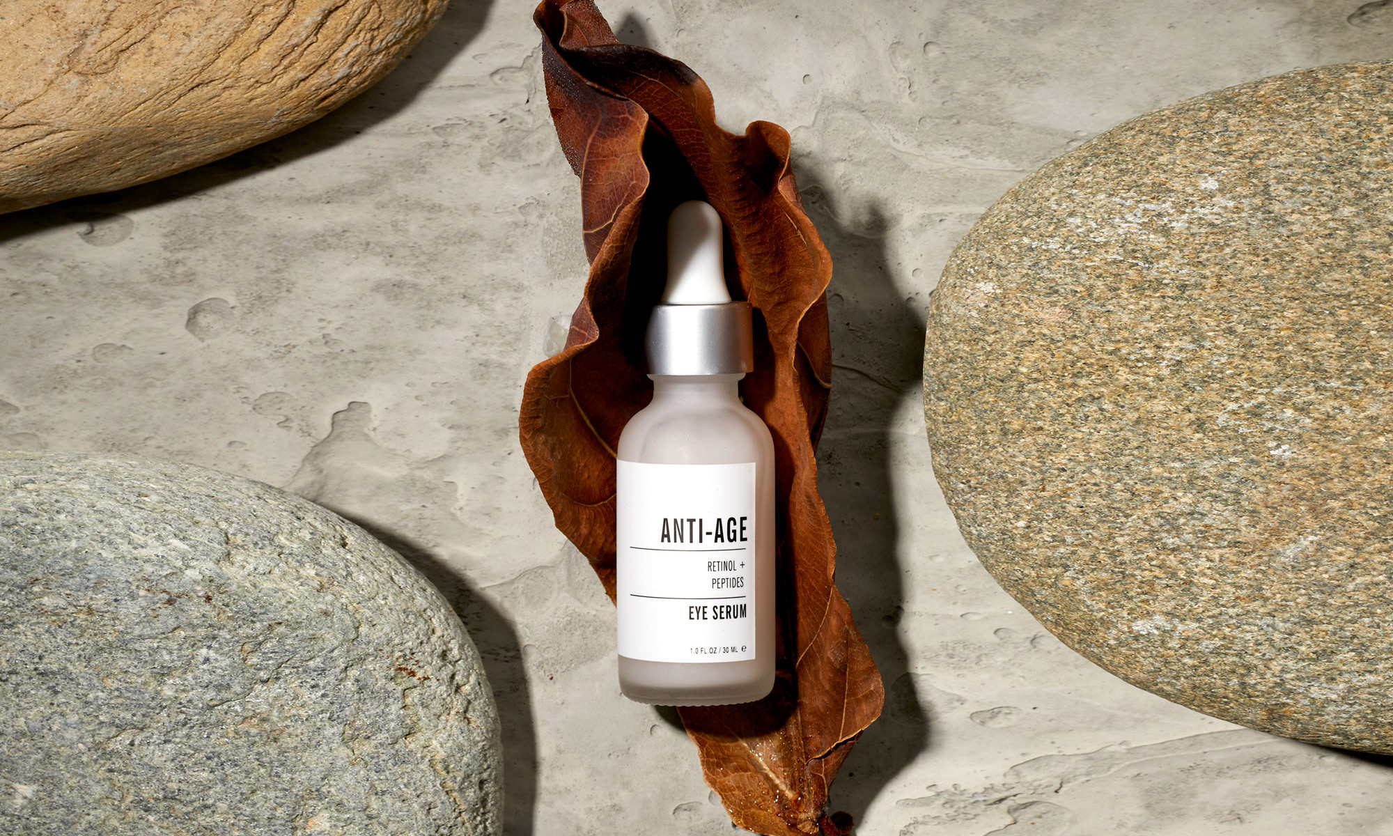Beautiful commercial product photography of anti-aging face serum surrounded by stones, leaves and other natural elements