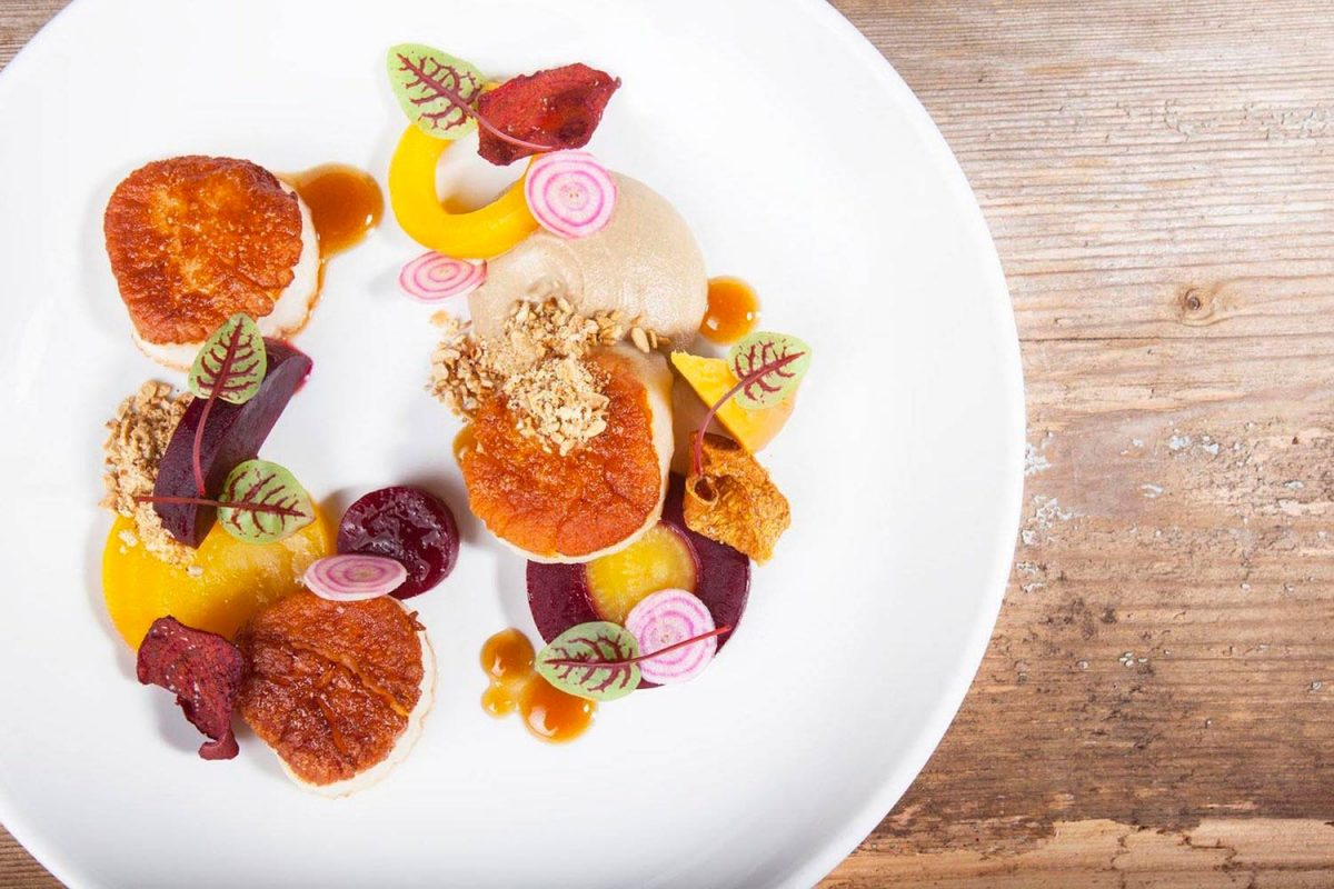 Commercial food photography showing modern plating of colorful scallops and vegetable dish