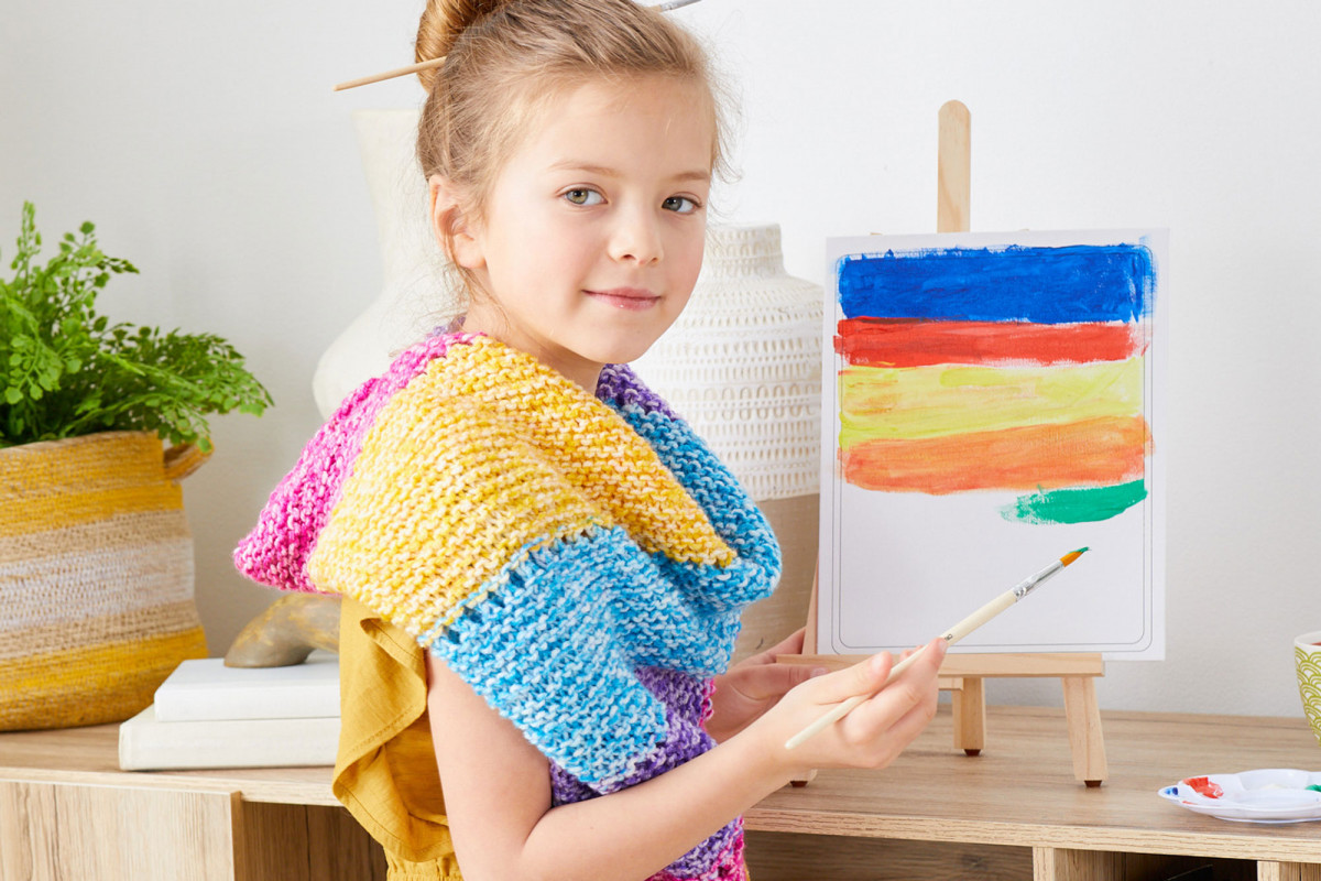 Lifestyle product photography of a young girl wearing a rainbow colored hand-knit scarf while painting