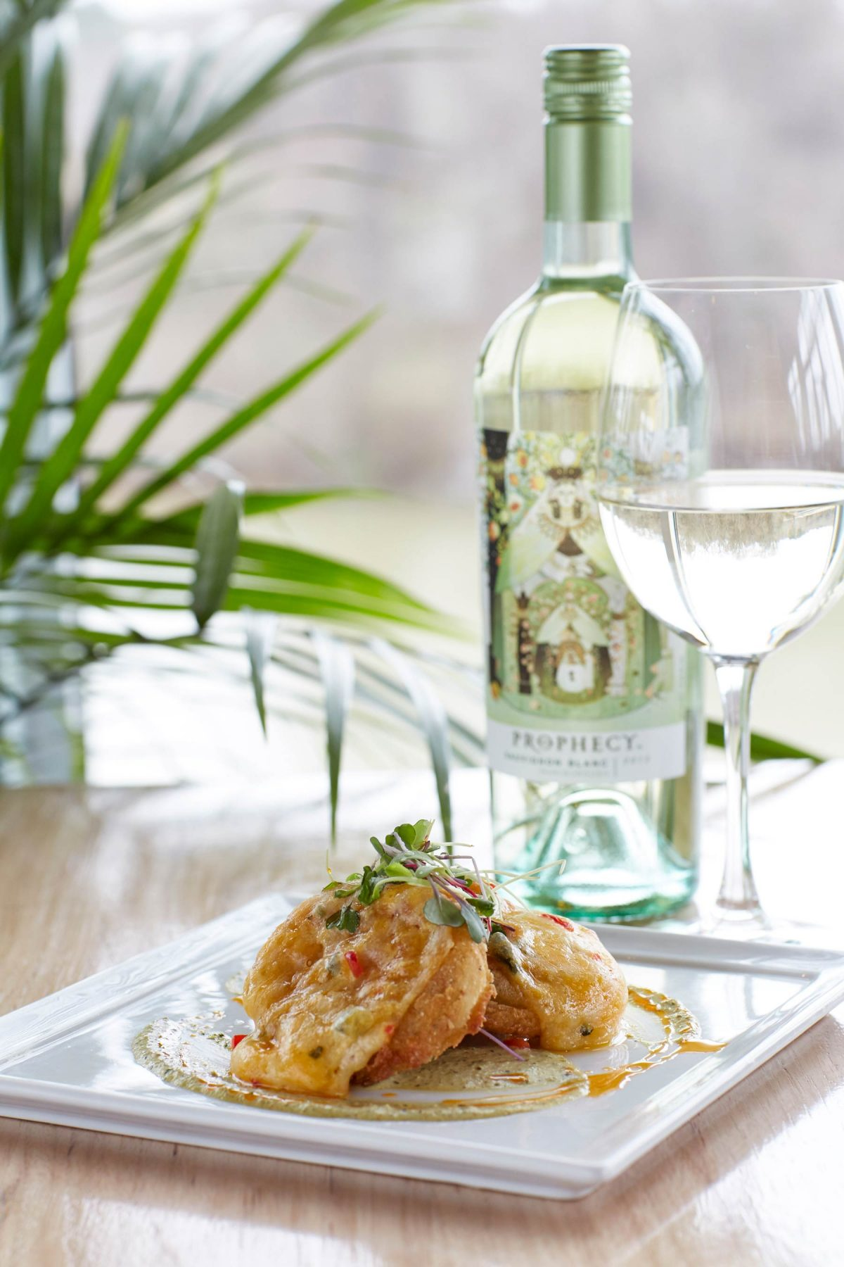 Food lifestyle photography of beautifully plated fried green tomatoes next to a bottle and glass of white wine on a wood table